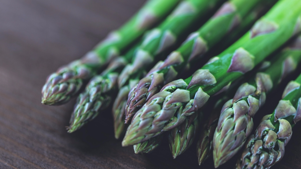 Healthy fresh asparagus resting on table